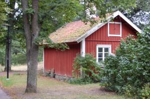 Ett litet rött hus bland lummiga träd.