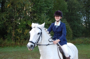 En tjej som sitter på en vit häst.