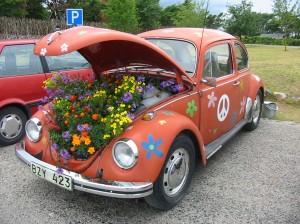 En gammal bil målad med blommor och med blommor i motorhuven.