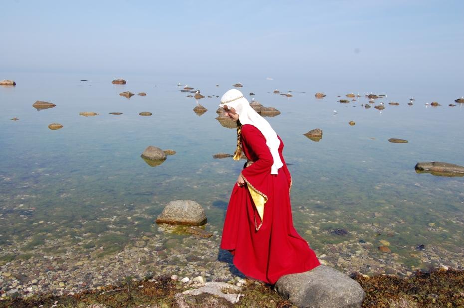 Vadar i havet i röd medeltidsklänning och slöja.