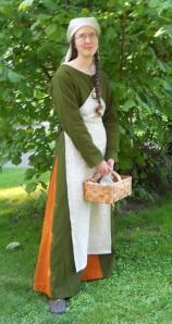 Grön och orange ylleklänning med vitt förkläde.