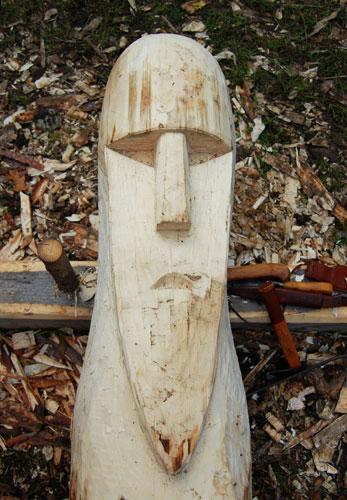 Ansiktet av en forntidsgud utmejslad i en trädstam.