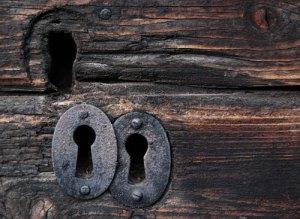 Gamla, smidda nyckelhål på en dörr av mörkt trä som bär spår av tiden.