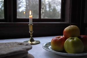 Knäckebröd, äpple och levande ljus på vit duk framför fönster