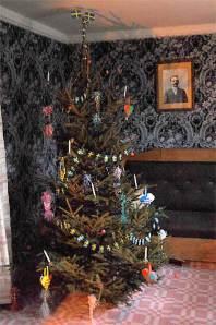 Julgran pyntad med svenska flaggor, ljus, smällkarameller och flätade hjärtan.