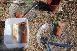 Tallrikar och låda med pannkakor som står i gräset.