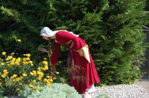 Luktar på blommor i röd medeltidsklänning