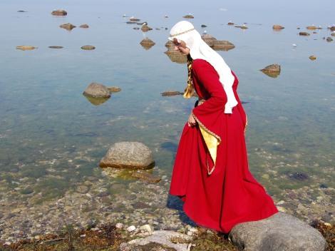 Röd ylleklänning med vida ärmar och vid fåll, vit linneslöja.