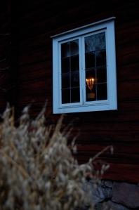 Levande ljus i fönstret i ett gammalt falurött hus