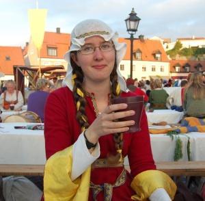 Skålar i röd medeltidsklänning och tunn slöja.
