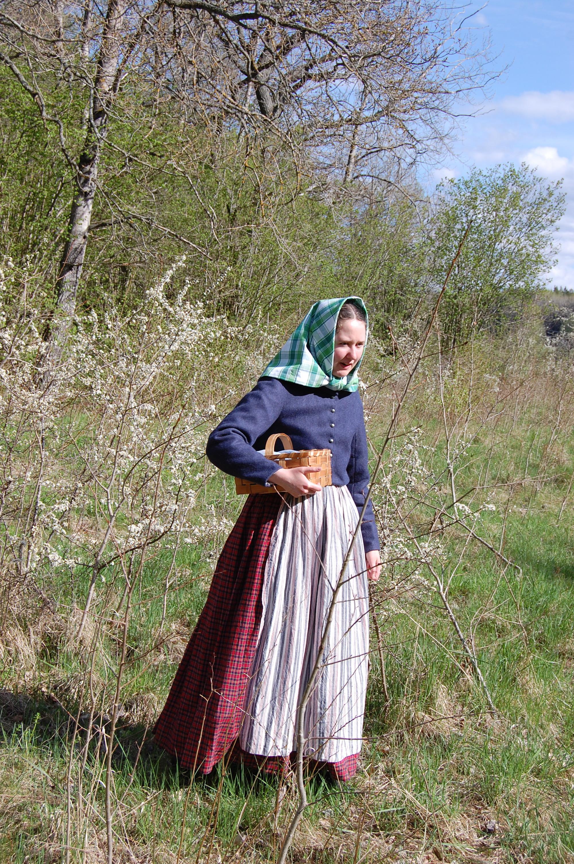 I 1850-talsklänning, förkläde, sjalett och vadmalsjacka, med korg, bland blommande slån.