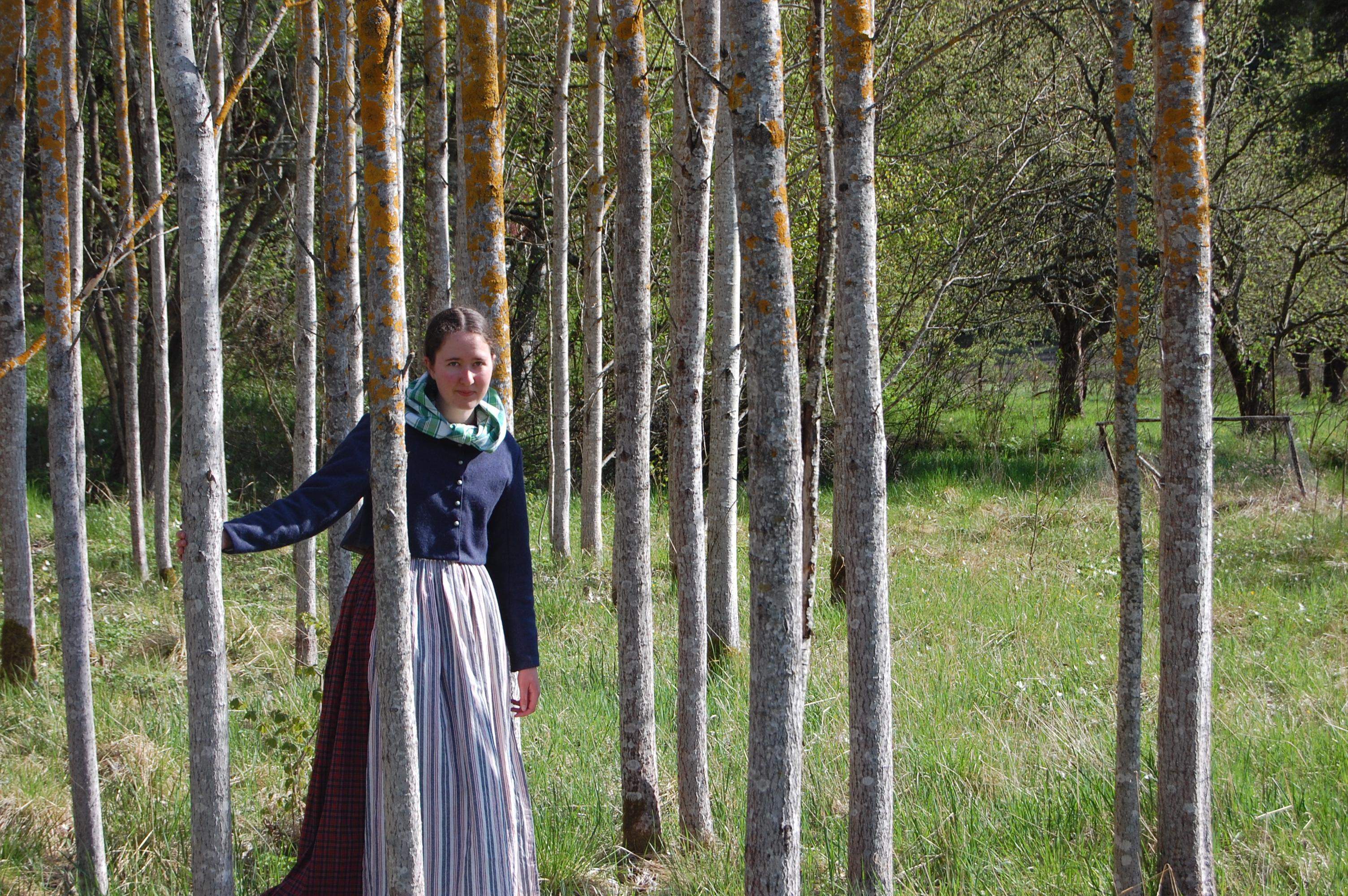 Bland trädstammar i rutig klänning, förkläde, vadmalsjacka och halskläde.