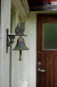 Gammal ringklocka i järn med kattmotiv