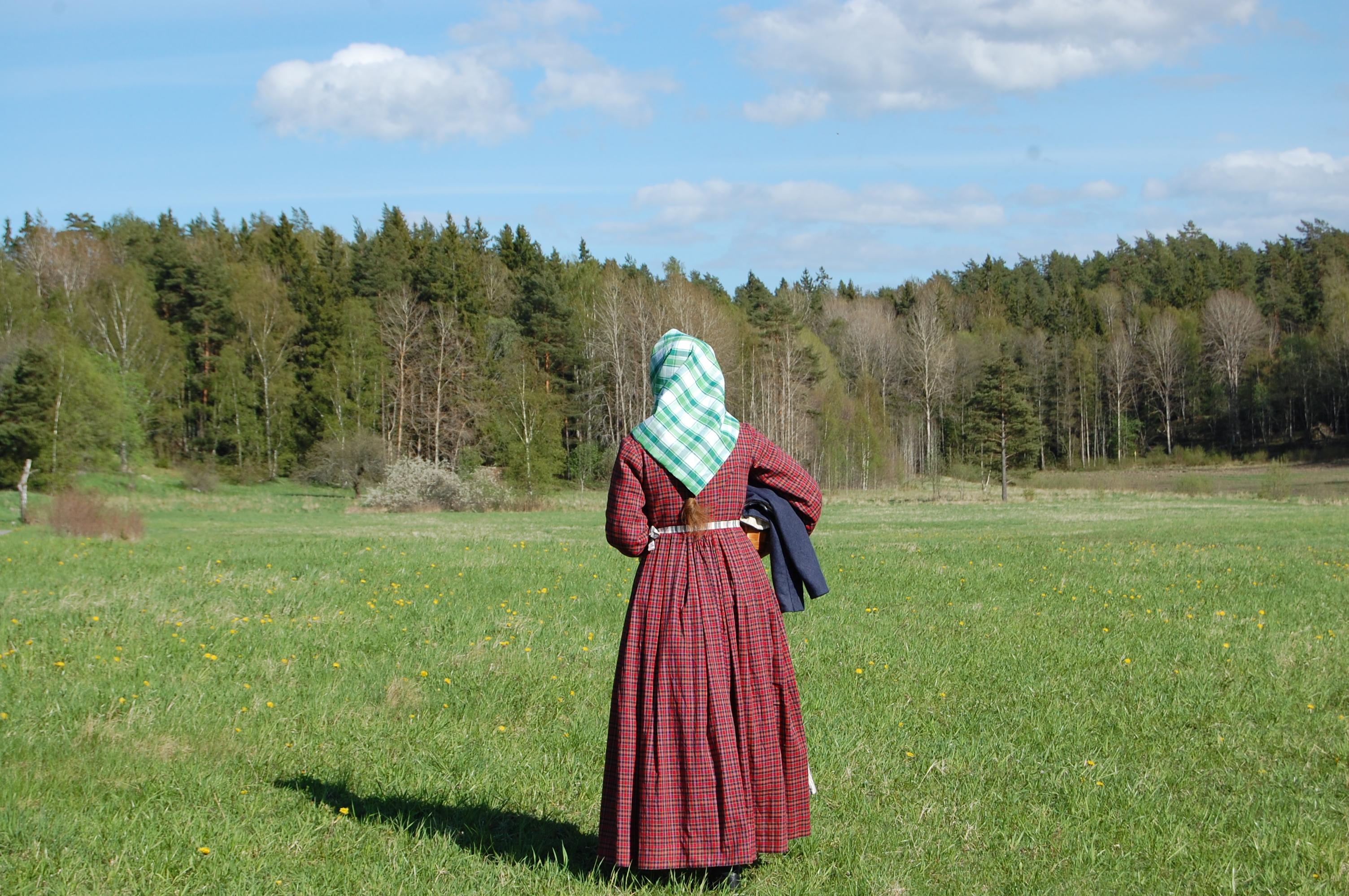 Bakifrån i rutig 1850-talsklänning och sjalett
