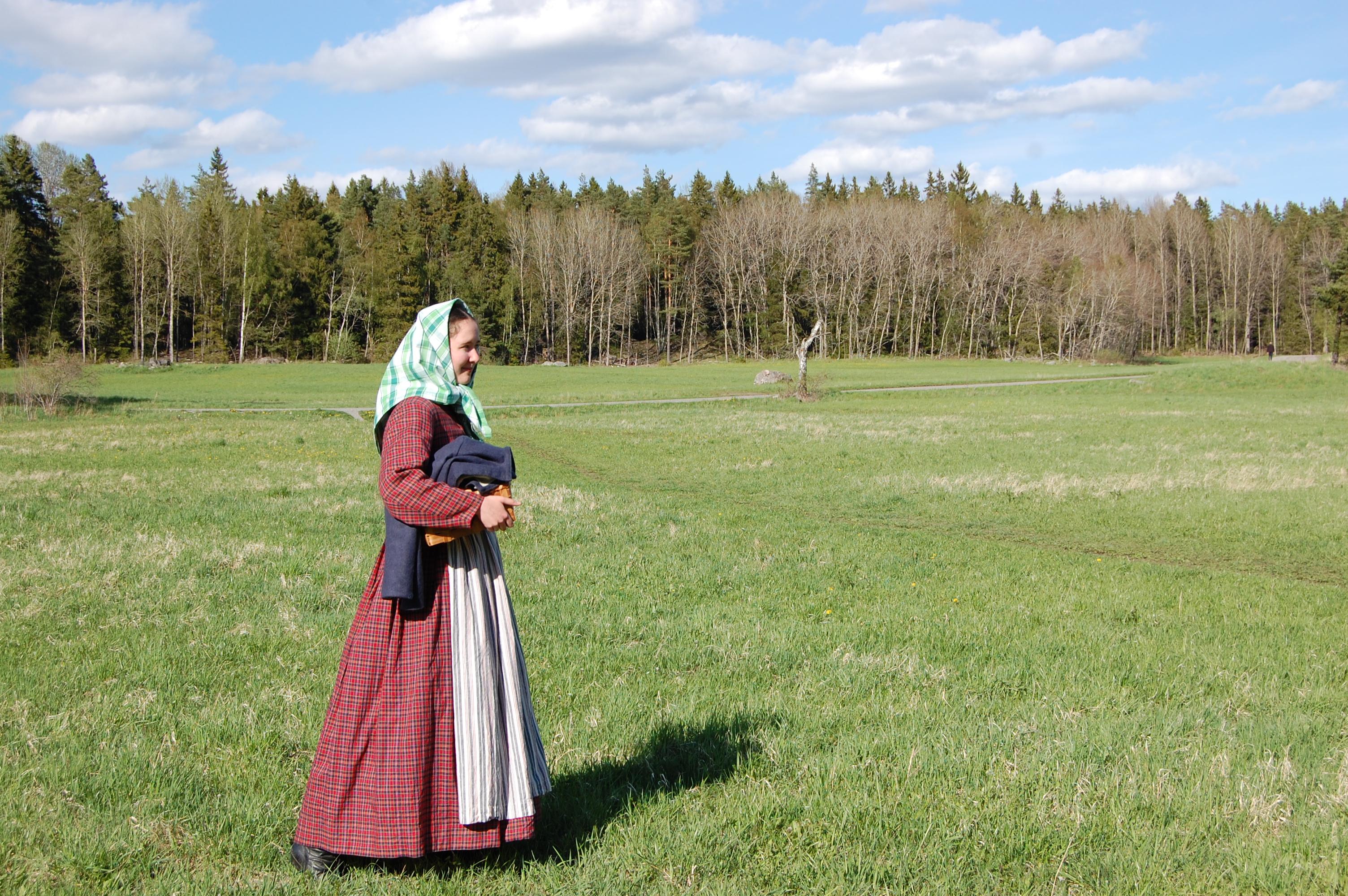 I rutig 1850-talsklänning och sjalett på stor äng