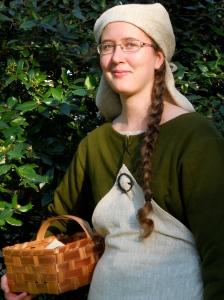 I grön medeltidsklänning samt huvudbonad och förkläde i oblekt linne.