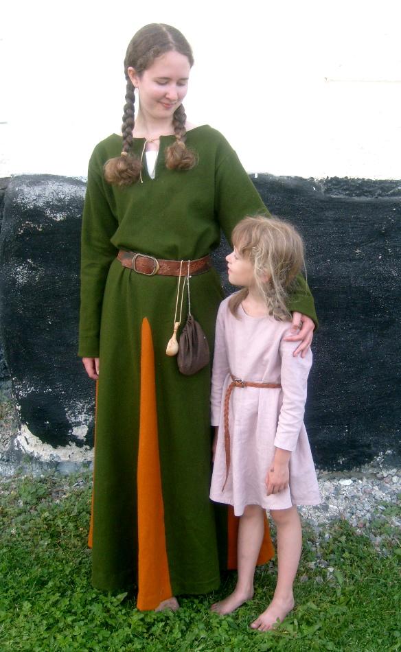 I grön medeltidsklänning intill liten flicka i gammalrosa kolt
