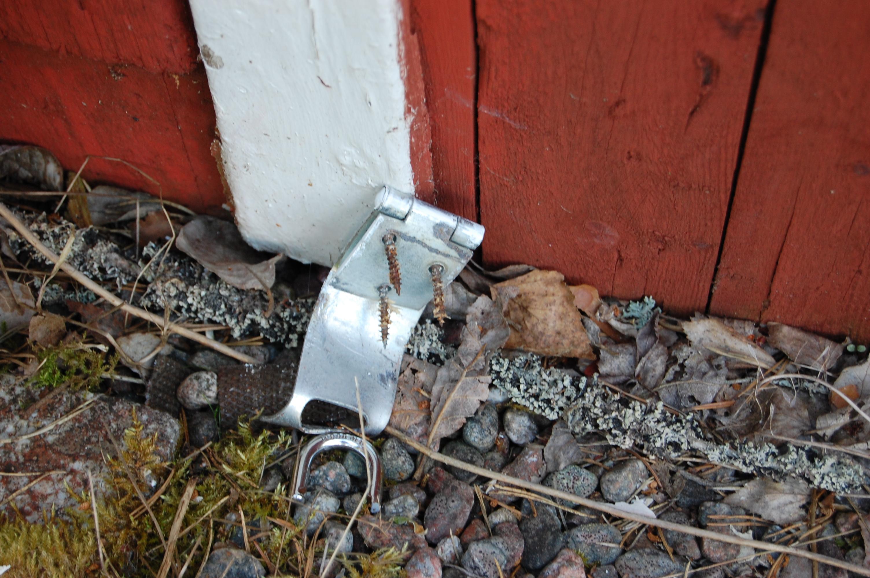Bortslitet lås på marken intill en faluröd vägg.