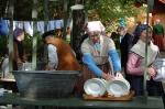 Tidstypiskt klädd kvinna som diskar porslin i en stor zinkbalja