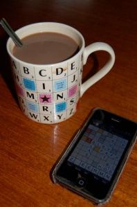 Mugg med alfapet-motiv och en iPhone med Betapet igång