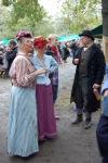 Två kvinnor och en man utstyrda i grälla sekelskifteskläder