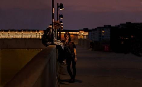 Två ensamma barn på en bro i kvällsmörker