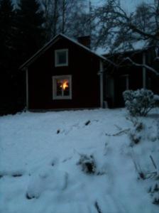 Stuga med adventsstjärna lysande i fönstret, snö och mörker runt omkring.