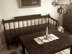 Svartvit bild föreställande en gammal utdragssoffa i mörkt trä, ett soffbord med duk och ljusstake.