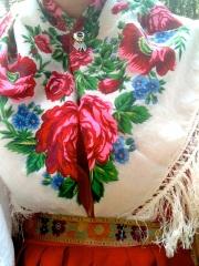 Närbild på ett halskläde, vitt med rosor i rosa och blått.